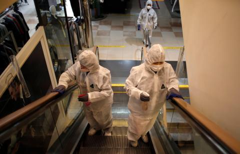 Empleados con equipo de protección rocían desinfectante como medida de precaución contra el coronavirus en unos grandes almacenes de Seúl, Corea del Sur, el 2 de marzo de 2020.