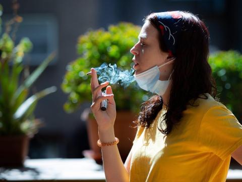 Una mujer con mascarilla, fumando, 6 de junio de 2020 en Madrid, España. .