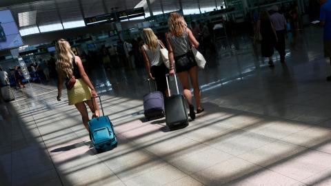 3 jóvenes se dirigen a su puerta de embarque en el aeropuerto de Barcelona-El Prat