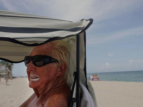 Henry Fraser usando óxido de zinc en los labios mientras se sienta a la sombra durante una visita a la playa.