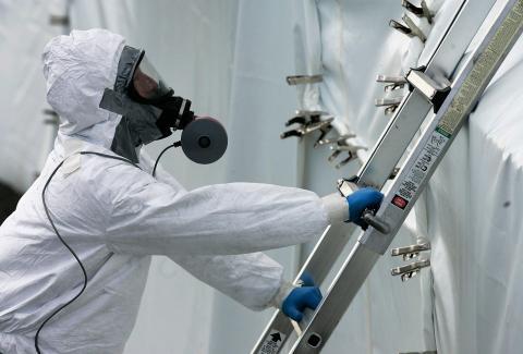 Técnico biológico con un traje de protección PAPR de Nivel C sube una escalera para inspeccionar una carpa de descontaminación que cubre el ayuntamiento de Smailholm, al sur de Escocia el 6 de marzo de 2007.