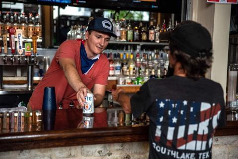 Un camarero sirve una bebida a un cliente en un bar de Austin, Texas, el 22 de mayo de 2020, el día en que los bares de la ciudad reabrieron del cierre por coronavirus.