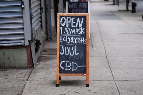 Un negocio muestra un cartel de venta de mascarillas, cigarrillos electrónicos y CBD durante la pandemia de coronavirus, el 27 de mayo de 2020, en Nueva York, EEUU.