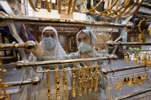 Dos mujeres con mascarilla mirando joyas de oro