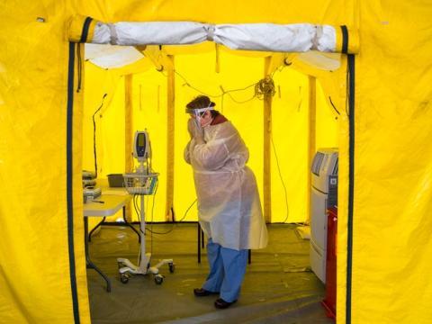 Una enfermera practicante se pone el equipo de protección en una tienda de campaña en el estacionamiento del Hospital Newton-Wellesley en Newton, Massachusetts, el 16 de marzo.