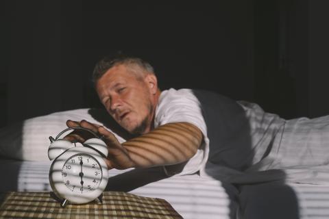 Hombre cansado en la cama apagando el despertador.