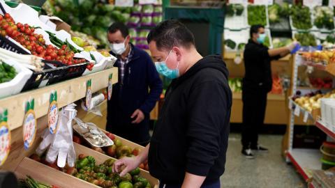 Un hombre con mascarilla compra verduras en un mercado