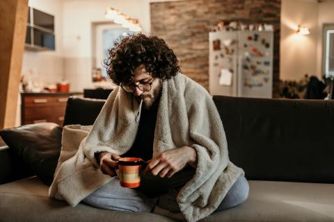 Hombre midiendo la temperatura con un termómetro para saber si tiene fiebre.