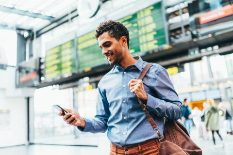 Hombre con un móvil en una estación de tren.