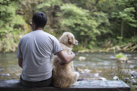 Hombre con un perro en el río.