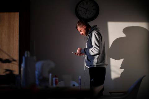 Un italiano mira su móvil en casa durante el confinamiento.