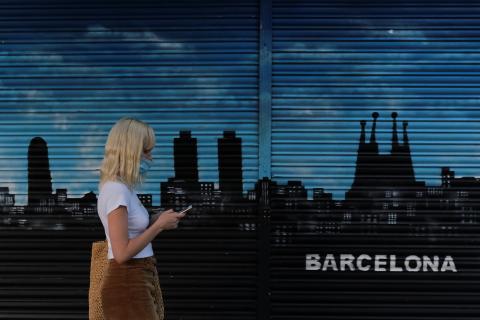 Una joven pasea con una mascarilla por delante de un mural pintado en Barcelona