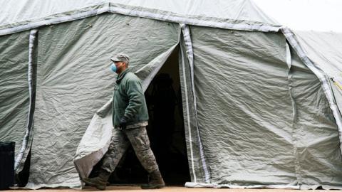 Un miembro de la Fuerza Aérea sale de una tienda de campaña construida como morgue improvisada en las afueras del Hospital Bellevue, el 25 de marzo de 2020 en la ciudad de Nueva York.
