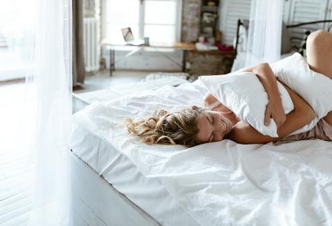 Una mujer abraza su almohada.