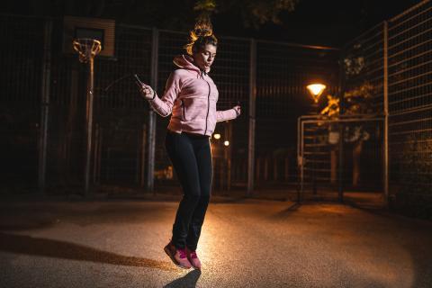Una mujer hace ejercicio en la noche.