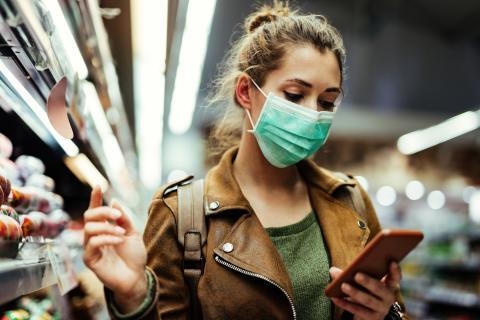 mujer haciendo la compra y mirando el móvil