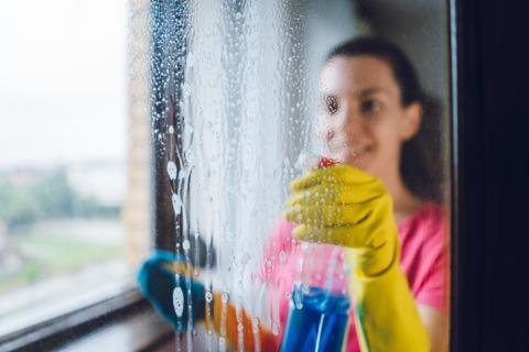 Mujer limpiando cristales.