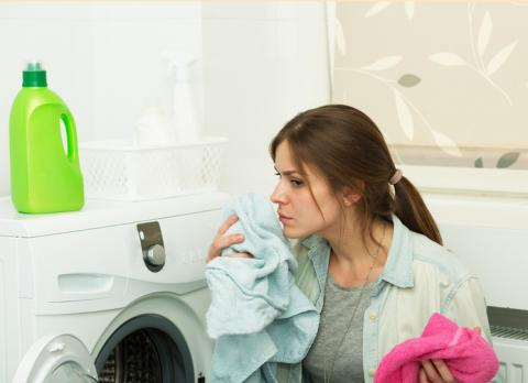 Mujer oliendo ropa.