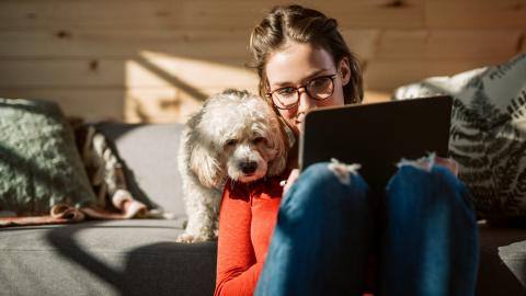 Mujer con un perro mirando el ordenador.