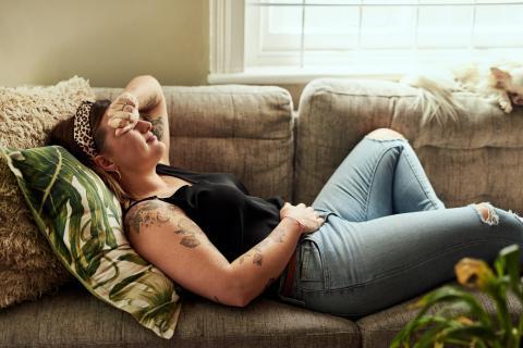 Mujer con la regla echada en el sofá.