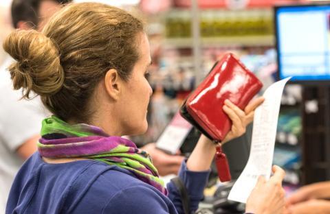 mujer revisa ticket de compra en supermercado