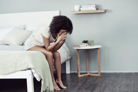 Mujer sentada en la cama.