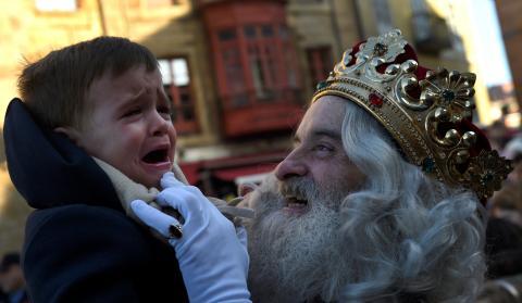 Un niño llora en brazos de un rey mago durante la cabalgata navideña de Gijón