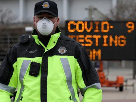 Un oficial de policía guía el tráfico en un estacionamiento de Denver donde la Guardia Nacional Aérea de Colorado está haciendo pruebas a personas que sospechan que tienen COVID-19, el 14 de marzo.