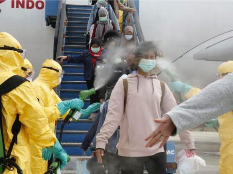 Los pasajeros indonesios que llegan de Wuhan son rociados con desinfectante en el aeropuerto Hang Nadim de Batam, el 2 de febrero.