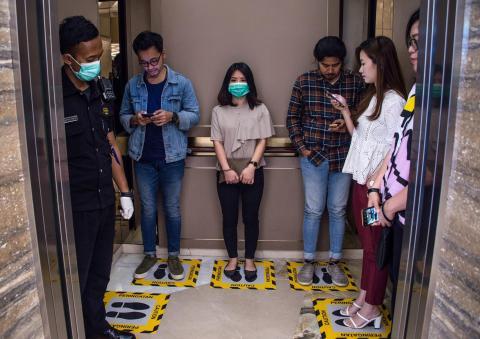 Personas en áreas designadas para asegurar el distanciamiento social dentro de un ascensor en un centro comercial en Surabaya, Indonesia, el 19 de marzo de 2020.
