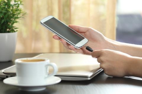 Persona cargando el móvil en una cafetería.
