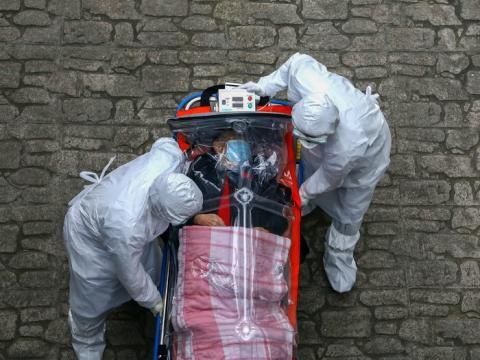 El personal médico con equipo de protección traslada a un paciente con coronavirus de una ambulancia a un hospital en Seúl, el 9 de marzo.
