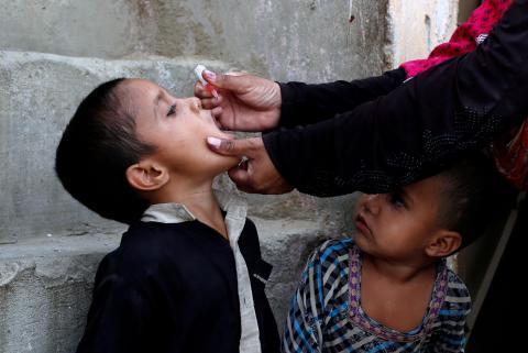 Vacunan a un niño contra la poliomielitis, durante una campaña contra la enfermedad, en un barrio pobre en Karachi, Pakistán, el 9 de abril de 2018.