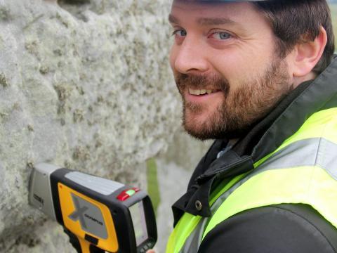 El investigador Jake Ciborowski analiza una piedra sarsen en Stonehenge utilizando un espectrómetro de fluorescencia de rayos X portátil.