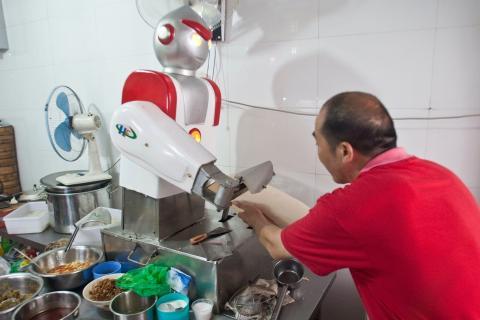 Un restaurante en Hangzhou, China, tiene un chef robot que se parece a Ultraman, un personaje de anime japonés. Este chef robot corta fideos en la cocina.