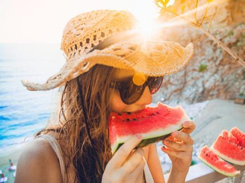 Una chica comiéndose una sandía.