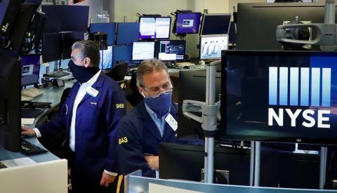 Traders con mascarillas observan la cotización de las acciones en Wall Street
