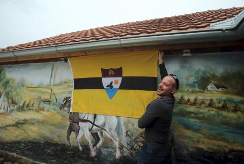 Un hombre muestra la bandera de Liberland en la aldea de Backi Monostor, Serbia, el 1 de mayo de 2015.