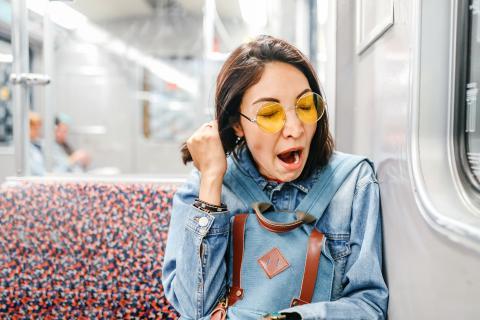 Chica bosteza en el metro.