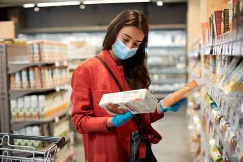 Chica compara productos en el supermercado.