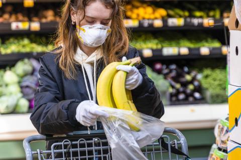 Chica comprando plátanos en un supermercado con mascarilla y guantes.
