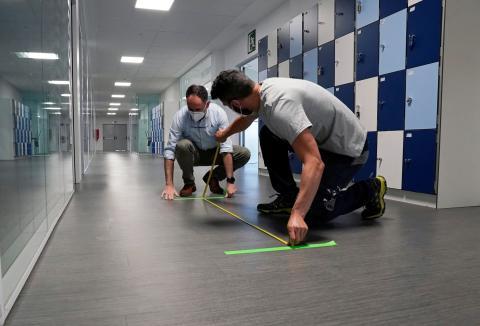 El director del colegio Ikastola Axular, Aitor Uriondo, y un asistente miden los marcadores de distancia social en medio del brote de la enfermedad por coronavirus en San Sebastián, el 21 de mayo de 2020.