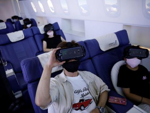 Customers in flight seats use virtual reality (VR) devices at First Airlines, that provides VR flight experiences, including 360-degree tours of cities and meals in Tokyo, Japan, on August 12, 2020. Kim Kyung-Hoon/Reuters