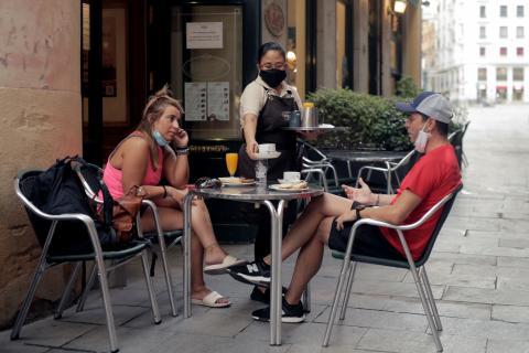 Dos jóvenes tomando algo en una terraza en Madrid.
