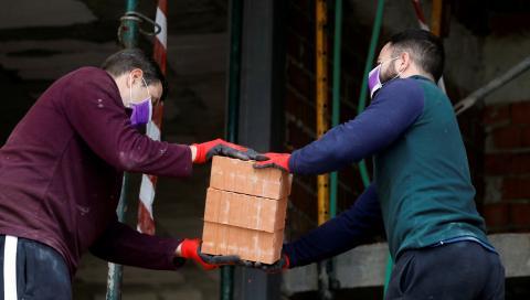 Dos obreros transportan ladrillos en la construcción de una vivienda en Ronda (Málaga)
