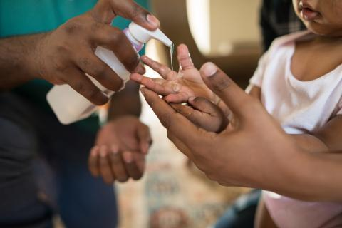Echar gel desinfectante a un niño.