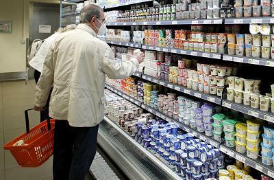 Un hombre cogiendo algo de la estantería de un supermercado