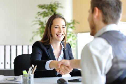 Un hombre y una mujer se dan un apretón de manos en la oficina