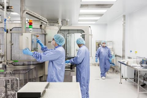 Los técnicos de laboratorio operan una máquina para lavar los frascos vacíos de remdesivir en una instalación de Gilead Sciences en La Verne