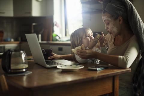 Madre con su hijo en el ordenador mientras come.